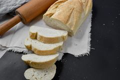 Bakery - rustic crusty loaves of bread and rolling pin on black chalkboard background. Still life captured from above. Layout with free copy space stock photography