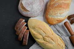 Bakery - rustic crusty loaves of bread and rolling pin on black chalkboard background. Still life captured from above. Layout with free copy space royalty free stock images