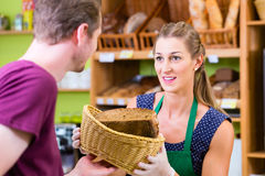 Bakery saleswoman offering bread Stock Image