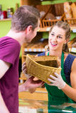 Bakery saleswoman offering bread Royalty Free Stock Photos