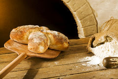 Bakery scene with rustic swiss bread. Taking swiss bread from the oven Stock Photo