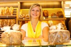Bakery shopkeeper posing in shop. Bakery saleswoman or shopkeeper posing in baker's shop Stock Photography