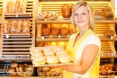 Bakery shopkeeper presents doughnuts Stock Photo
