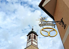 Bakery sign with pretzel  beside a church tower Stock Photos