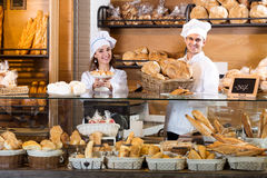 Bakery staff offering bread and different pastry. Attractive bakery staff offering bread and different pastry for sale Stock Images