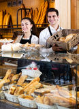 Bakery staff offering bread and different pastry. Attractive seller staff offering bread and different pastry for sale Royalty Free Stock Images