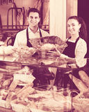 Bakery staff offering bread and different pastry. Cheerful seller staff offering bread and different pastry for sale Stock Photography