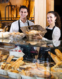 Bakery staff offering bread and different pastry. Cheerful seller staff offering bread and different pastry for sale Royalty Free Stock Photo