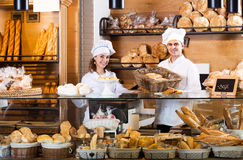 Bakery staff offering bread and different pastry. Friendly bakery staff offering bread and different pastry for sale Royalty Free Stock Photo
