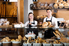 Bakery staff offering bread and different pastry. Happy bakery staff offering bread and different pastry for sale Stock Photo