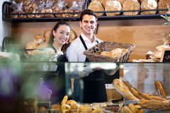 Bakery staff offering bread and different pastry. Happy seller staff offering bread and different pastry for sale Royalty Free Stock Photos