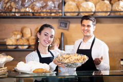 Bakery staff offering bread and different pastry. Happy young seller staff offering bread and different pastry for sale Royalty Free Stock Images