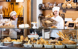 Bakery staff offering bread and different pastry. Helpful bakery staff offering bread and different pastry for sale Royalty Free Stock Photos