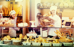 Bakery staff offering bread and different pastry. Helpful bakery staff offering bread and different pastry for sale Royalty Free Stock Images
