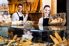 Bakery staff offering bread and different pastry. Neat seller staff offering bread and different pastry for sale Royalty Free Stock Photography