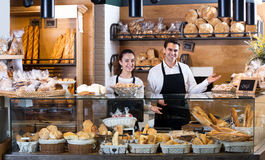 Bakery staff offering bread and different pastry. Portrait friendly seller staff offering bread and different pastry for sale Royalty Free Stock Photos