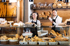 Bakery staff offering bread and different pastry. Portrait happy seller staff offering bread and different pastry for sale Royalty Free Stock Images