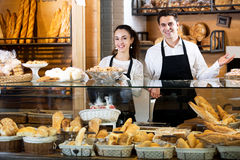 Bakery staff offering bread and different pastry. Portrait neat seller staff offering bread and different pastry for sale Royalty Free Stock Photos