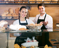 Bakery staff offering bread and different pastry. Portrait young seller staff offering bread and different pastry for sale. Focus on the woman Royalty Free Stock Image