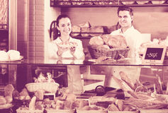 Bakery staff offering bread and different pastry. Positive bakery staff offering bread and different pastry for sale Royalty Free Stock Images