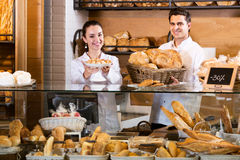 Bakery staff offering bread and different pastry. Positive bakery staff offering bread and different pastry for sale Stock Image