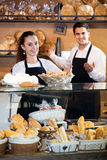 Bakery staff offering bread and different pastry. Positive young seller staff offering bread and different pastry for sale. Focus on the woman Royalty Free Stock Image