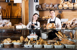 Bakery staff offering bread and different pastry. Smiling bakery staff offering bread and different pastry for sale Royalty Free Stock Image