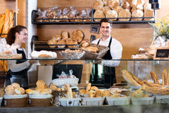Bakery staff offering bread and different pastry. Smiling young seller staff offering bread and different pastry for sale Stock Photo
