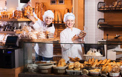 Bakery staff offering bread. Happy bakery staff offering bread and different pastry for sale Royalty Free Stock Photos