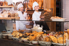 Bakery staff offering bread Stock Image