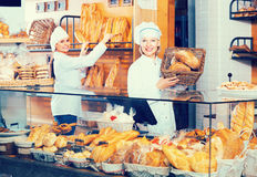 Bakery staff offering bread Royalty Free Stock Photos