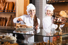 Bakery staff offering bread Stock Images