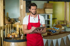 Bakery staff writing on clipboard at counter. In bake shop Stock Image