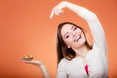 Smiling woman holds cake in hand pointing with finger Stock Image