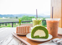 Bakery. Thai iced milk tea, Thai milk tea crepe cake, iced matcha green tea, matcha green tea roll cake on a wooden tray and table at the bakery shop located in Stock Photography