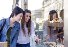 Bakery Window Shopping. Two young women admiring sweet treats through the window of a bakery Stock Photo