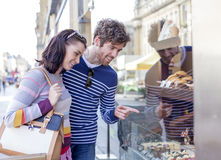 Bakery Window Shopping. Young couple admiring sweet treats through the window of a bakery Stock Photos