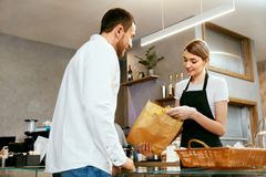 Bakery. Woman Working, Selling Bakery To Male. Bakery. Woman Working, Selling Fresh Bakery To Male Buyer. High Resolution Royalty Free Stock Photo