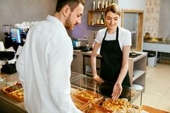 Bakery. Woman Working, Selling Bakery To Male. Bakery. Woman Working, Selling Fresh Bakery To Male Buyer. High Resolution Royalty Free Stock Image