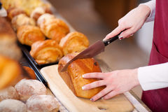 Bakery Worker Cutting Bread Loaf On Board Royalty Free Stock Image
