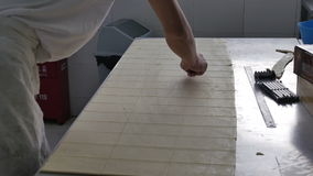 Bakery worker cutting dough sheets for croissants in industrial kitchen stock footage