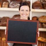 Bakery worker holding a blank chalkboard Royalty Free Stock Photos