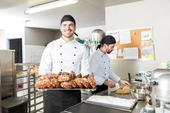Bakery Worker Holding Tray Of Pastries. Portrait of confident baker with sweet and tempting baked breads in kitchen royalty free stock photography