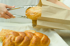Bakery worker placing loaf of bread inside brown paper bag using large silver tweezers Royalty Free Stock Photo