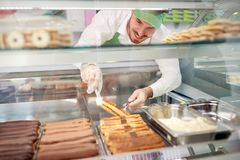 Bakery worker taking out biscuit cake from showcase stock photo