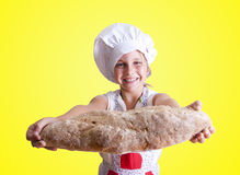 Bakery. Young girl in the kitchen with chef clothing Royalty Free Stock Photos