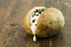 Bakes Potato with herbs. Baked Potato with curd and herbs lying on wood stock image