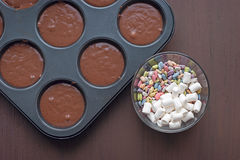 Bakeware on a dark wooden background. Jelly beans, marshmallows, cooking Stock Photos