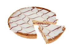 Bakewell tart. Bakewell pie chart, iced bakewell tart with a section cut out isolated against white stock photo