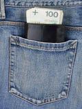 Bakficka av jeans med plånboken och pengar royaltyfria foton